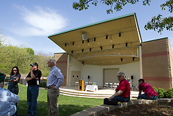 10 May 2014:  Steve Robinson sitting on blocks in red shirt looking at the camera at 25th anniversary celebration of the Constitution Trail ceremony at Connie Link Amphitheater in Normal Illinois