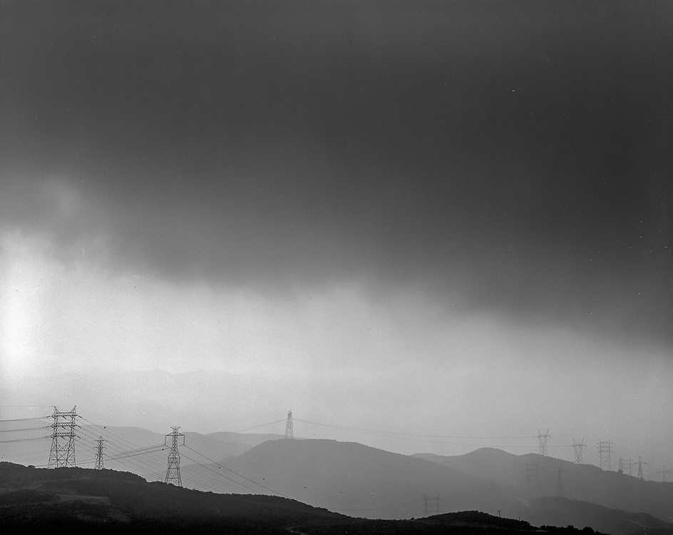 Moody black and white 4x5 film photograph of hills, power lines, and dark cloudy skies.