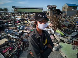 October 5, 2018 - Palu, Mid Sulawesi, Indonesia - A resident wears a mask as retrieval of dead bodies is ongoing at beach Talisha. Thousands of people died from 7.7 SR earth quake that a triggered tsunami which destroyed thousands of houses and buildings near the beach. (Credit Image: © Donal HusniZUMA Wire)