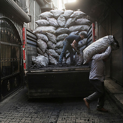 A worker unloads charcoal at a shop in the Savas neighborhood in the Sur district in Diyarbakir, Turkey, on March 21, 2017.