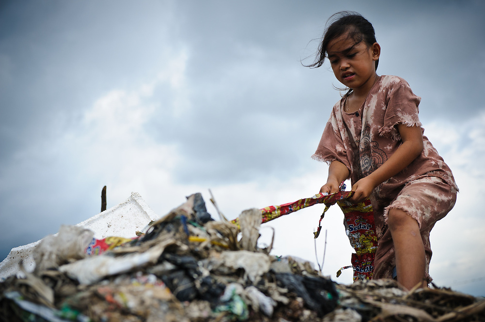 Annie, 11, collecting plastic and metal waste for recycling from an older section of the 'Trash mountain', Makassar, Sulawesi, Indonesia.