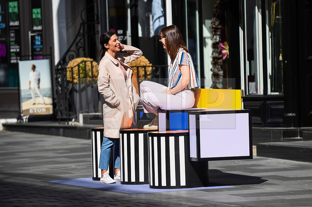 """© Licensed to London News Pictures. 14/09/2019. LONDON, UK.  Tourists sit on a sculptural bench as """"Walala Lounge"""" opens in Mayfair's South Molton Street.  Artist and designer Camille Walala's installation comprises 10 sculptural benches, accompanied by planters and a series of oversized flags strung, bunting-style, from shopfront to shopfront, converting the street into an immersive corridor of colour as part of this year's London Design Festival.  Photo credit: Stephen Chung/LNP"""