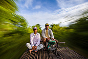 Two drivers of bamboo train, or Norry, speed along the railway track.
