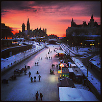 Sunset over the Rideau Canal, Parliament and the Chateau Laurier in Ottawa, ON. as skaters make their way along the Rideau Canal.