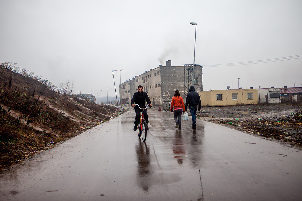 "Road to the segregated Roma settlement ""Budulovska Street"" (2016). In 2015 the ""muddy"" roads to and in the settlement were asphalted and the infrastructure for the residents  improved. The city has roughly 11200 inhabitants, about 1980 (18%) of them have Roma ethnicity and around 800 are living at the segregated settlement 'Budulovska Street' (2014)."