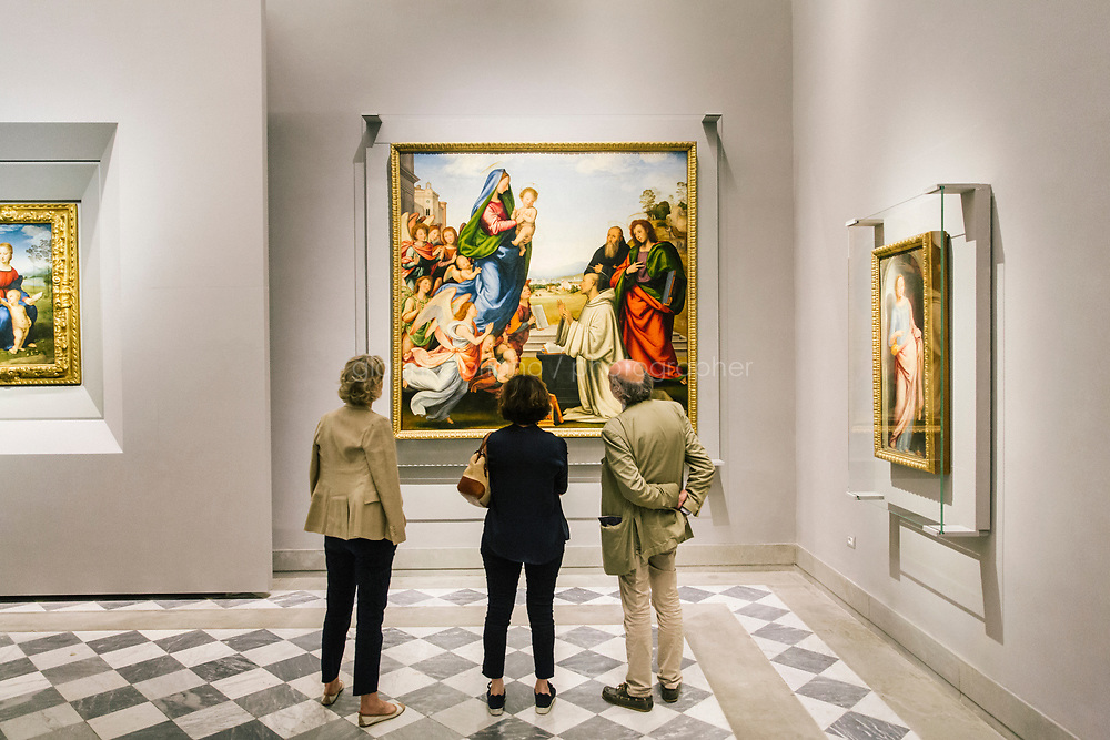 FLORENCE, ITALY - 3 JUNE 2018: Visitors looks at the &quot;Apparition of the Virgin to Saint Bernard&quot; by Fra Bartolomeo, in its new location in room 41 at the Uffizi, in Florence, Italy, on June 3rd 2018.<br /> <br /> As of Monday June 4th 2018, Room 41 or the &ldquo;Raphael and Michelangelo room&rdquo; of the Uffizi is part of the rearrangement of the museum's collection that has<br /> been defining Uffizi Director Eike Schmidt&rsquo;s grander vision for the Florentine museum.<br /> Next month, the museum&rsquo;s Leonardo three paintings will be installed in a<br /> nearby room. Together, these artists capture &ldquo;a magic moment in the<br /> first decade of the 16th century when Florence was the cultural and<br /> artistic center of the world,&rdquo; Mr. Schmidt said. Room 41 hosts, among other paintings, the dual portraits of Agnolo Doni and his wife Maddalena Strozzi painted by Raphael round 1504-1505, and the &ldquo;Holy Family&rdquo;, that Michelangelo painted for the Doni couple a year later, known as the<br /> Doni Tondo.