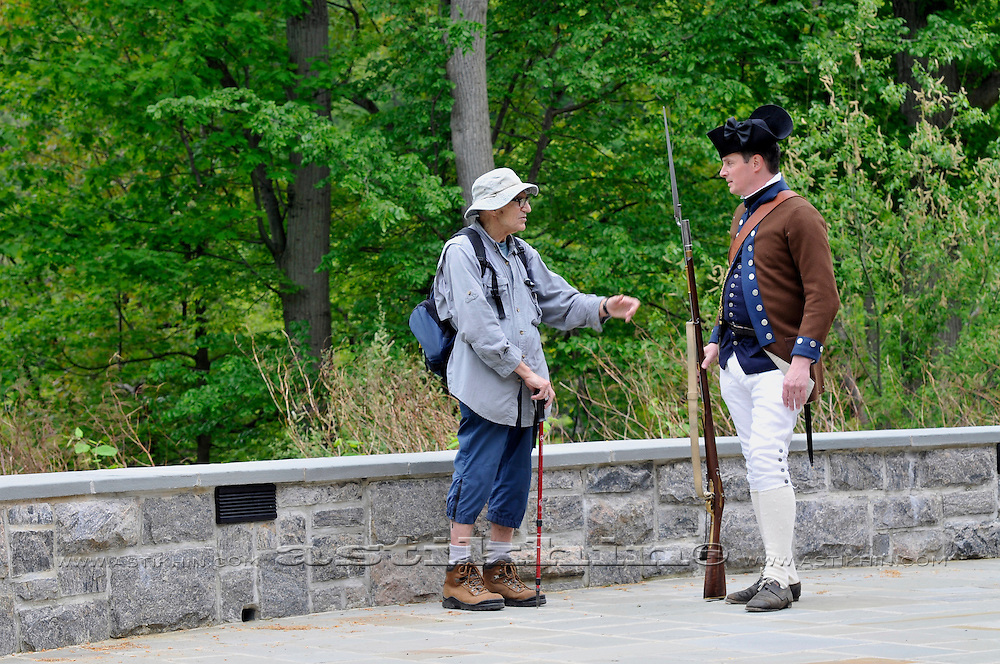 Soldier of American Revolution with Brown Bess musket in Fort Montgomery talking with old man.