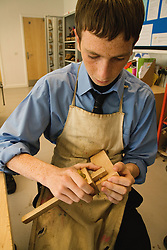Secondary school student using a mortice gauge in a Design technology lesson,