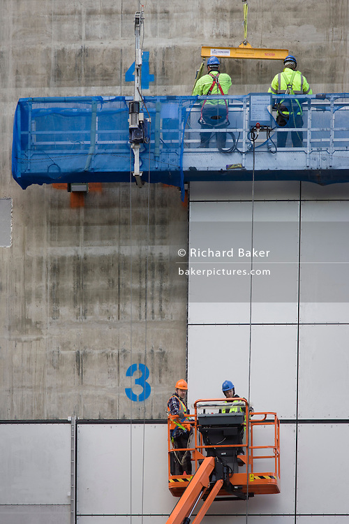 Workmen in cradles on wall of construction development in the City of London