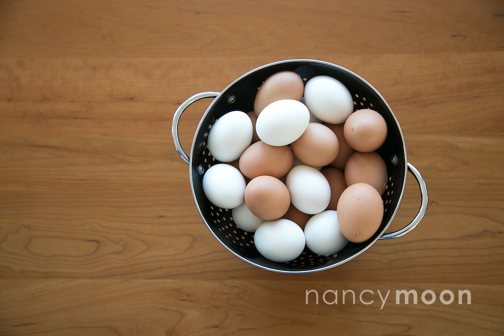 Brown and white eggs in a black colander.<br />