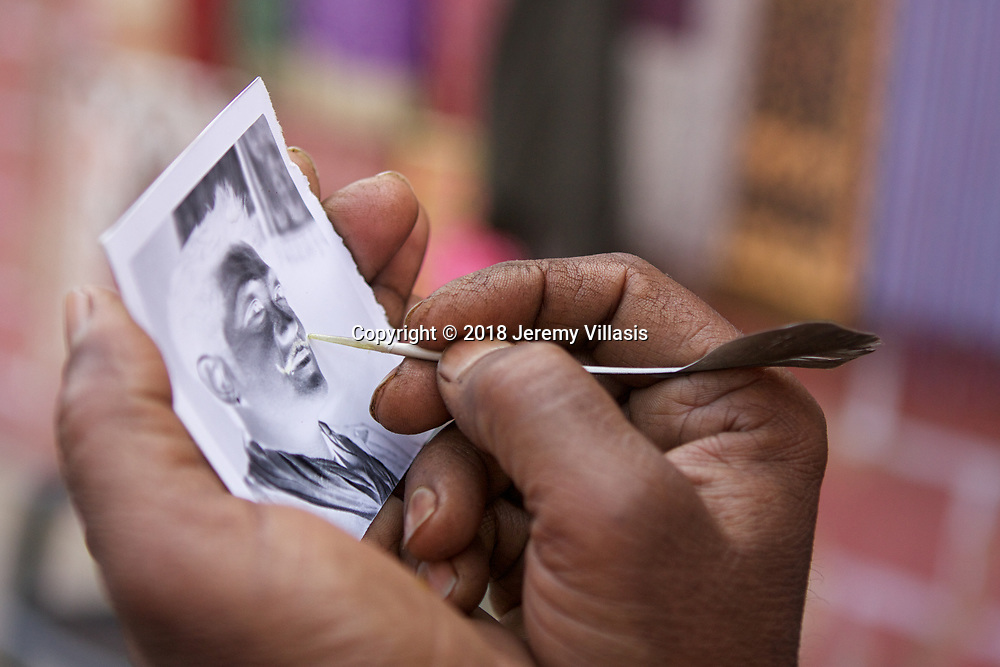 Tikam Chand paints a moustache on a customer's negative print using a feather. The print will be pinned on a wooden plate and placed in front of the camera again to produce a positive image.