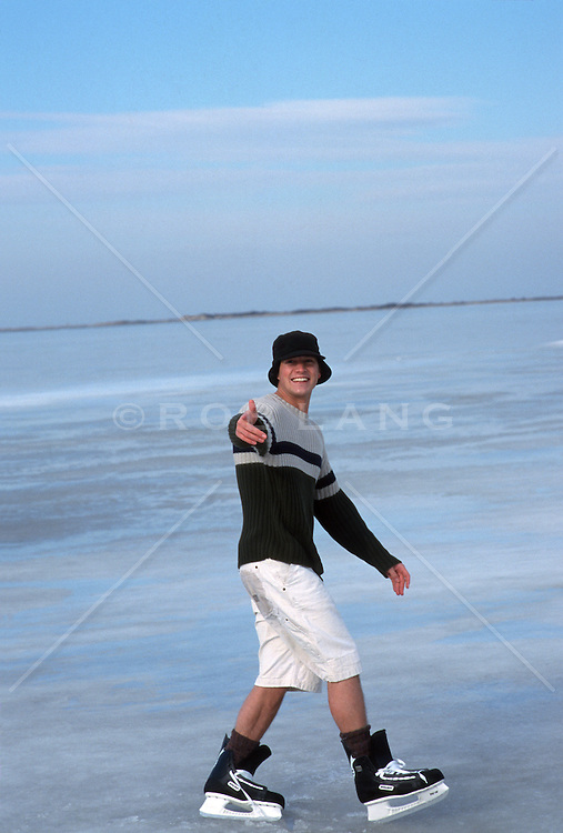 Young Man Ice Skating Outdoors in Shorts