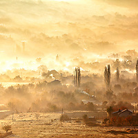 Village covered in autumn mists at sunrise
