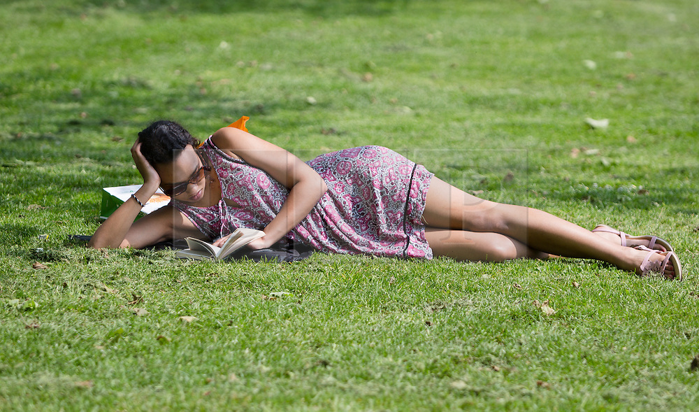 © Licensed to London News Pictures. 12/05/2016. LONDON, UK.  A woman lies on the grass reading a book during warm sunny weather in Green Park at lunchtime.  Photo credit: Vickie Flores/LNP