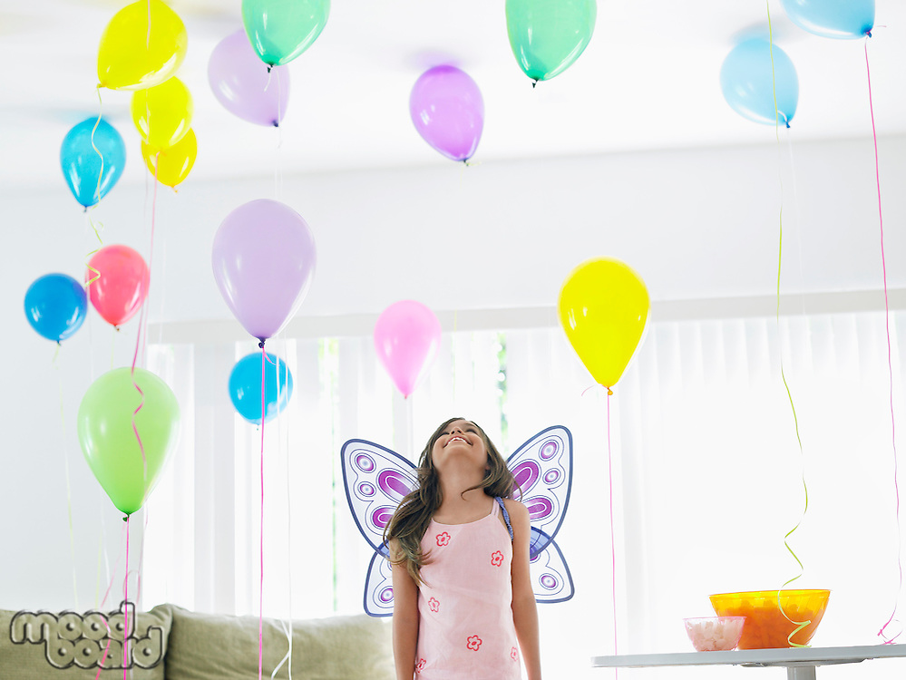 Young girl (7-9) with fairy wings in room full of balloons