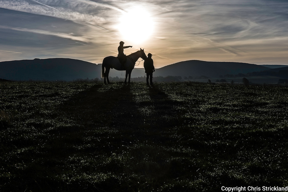 Bonchester Bridge, Hawick, Scottish Borders, UK. 29th September 2015. Foot and mounted followers of the Jedforest Hunt watch proceedings of an early morning fox hunt as the sun rises behind them.
