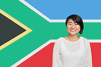 Portrait of young Asian woman smiling against South African flag