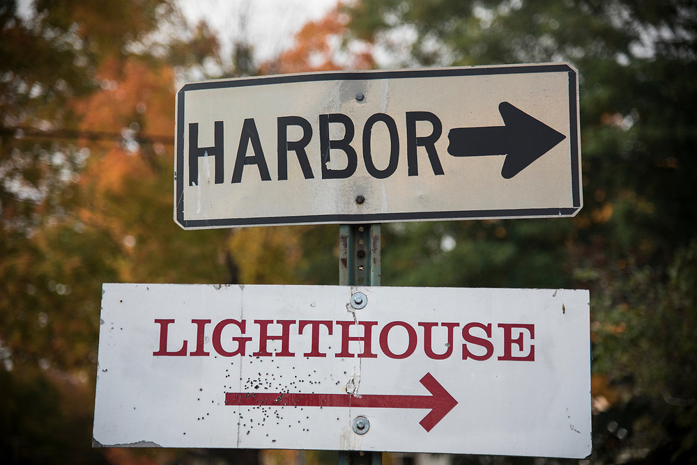 Signage for the harbor and lighthouse at Big Bay, Michigan. Sign has been damaged by a shotgun blast, a reflection of the rural character of the region.