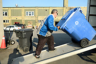 Man in blue jacket pushing large blue container up a ramp and into a truck in the Worth a Second Look parking lot in Kitchener, Ontario. The man is participating in Job Cafe, a work placement program of The Working Centre.