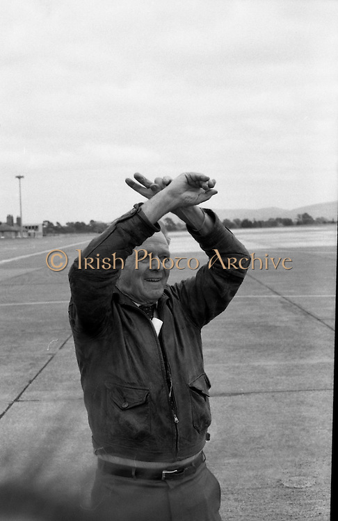 """Wrongway Corrigan"" at Baldonnell.  (R84)..1988..18.07.1988..07.18.1988..18th July 1988..Douglas ""Wrongway"" Corrigan returned to Baldonnell Airdrome 50 years after his transatlantic flight in a Curtiss Robin aircraft. After a transcontinental flight from California to New York, Mr Corrigan was to make a return flight to California. However on take off he took off over the Atlantic to Ireland. He had been refused permission from American authorities to fly solo to Ireland. On Arrival in Ireland he maintained that bad weather conditions and compass malfunction were the reason for his ""wrongway' flight..In 1938 he was met by Mr R W O'Sullivan as he disembarked from his plane..Comdt D K Johnston, Irish Air Corps flew in formation with Mr Corrigan in Irish Airspace..Mr J Maher,Aer Lingus Chief Engineer,hangared the aircraft on arrival and Mr V Ellis of Oriole Steamship Lines was responsible for the transportation of the aircraft back to the U.S. aboard the S S Lehigh.  These gentlemen were here today to meet again with Mr Corrigan...Portrait of ""Wrongway"" Corrigan standing on the tarmac at Baldonnell Aerodrome."