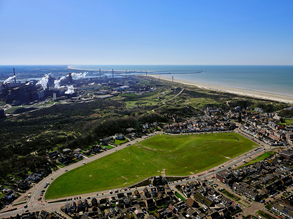 Nederland, Noord-Holland, Wijk aan Zee, 23-03-2020; dorp aan de Noordzee met de karakteristieke dorpsweide. In de achtergrond het staalbedrijf Tata Steel (het vroegere Hoogovens). Dochteronderneming Harsco, aan de grens van het industrieterrein, verwerkt slikken uit de staalfabriek veroorzaakt regelmatig grafietregens in Wijk aan Zee.<br /> Village on the North Sea with the characteristic village meadow. In the background the steel company Tata Steel (formerly Hoogovens). On the border of the industrial area, the Harsco factory processes mud from the steel factory and causes graphite rains in Wijk aan Zee.<br /> <br /> luchtfoto (toeslag op standaard tarieven);<br /> aerial photo (additional fee required)<br /> copyright © 2020 foto/photo Siebe Swart
