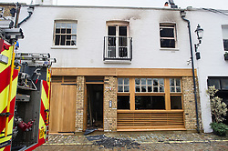 © London News Pictures. 22/01/2014. London, UK. View of the front entrance showing fire damage. The scene of a fire at a £3 million property on Hyde Park Gardens Muse, one of the most expensive street in London. The grade 2 listed building was gutted by a fire that started in the basement. Eight fire engines and 58 firefighters and officers attended the scene. There have been no reports of injuries. Photo credit: Ben Cawthra/LNP