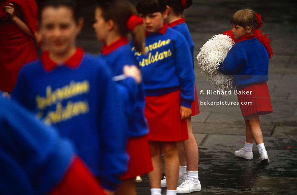 Members of the Coleraine majorette troupe march through the wet streets of Belfast, Northern Ireland. Getting ready for their march through city streets, the young girls wear identical uniforms and colours. The youngest gathers her pom poms and walks to her position in the parade.