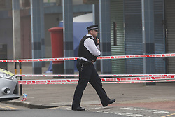 © Licensed to London News Pictures. 03/04/2017. LONDON, UK.  A police officer walks past the forensic tent at the crime scene and police cordon around BJ Wines and parade of shops in Freemasons Road, Canning Town, east London. Ahmed Jah, 21 is reported to have been knifed inside the off license, BJ Wines in Freemasons Road yesterday afternoon after he was set upon by a gang of men and stabbed in the chest. Emergency ambulance services attended and the man was pronounced dead at the scene shortly after.  Photo credit: Vickie Flores/LNP
