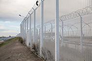 Calais, Pas-de-Calais, France - 17.10.2016    <br />  <br /> High fences separate the camp from the highway to the port. &rdquo;Jungle&quot; refugee camp on the outskirts of the French city of Calais. Many thousands of migrants and refugees are waiting in some cases for years in the port city in the hope of being able to cross the English Channel to Britain. French authorities announced that they will shortly evict the camp where currently up to up to 10,000 people live.<br /> <br /> Hohe Zaeune trennen das Camp von der Schnellstra&szlig;e zum Hafen. &rdquo;Jungle&rdquo; Fluechtlingscamp am Rande der franzoesischen Stadt Calais. Viele tausend Migranten und Fluechtlinge harren teilweise seit Jahren in der Hafenstadt aus in der Hoffnung den Aermelkanal nach Gro&szlig;britannien ueberqueren zu koennen. Die franzoesischen Behoerden kuendigten an, dass sie das Camp, indem derzeit bis zu bis zu 10.000 Menschen leben K&uuml;rze raeumen werden. <br /> <br /> Photo: Bjoern Kietzmann