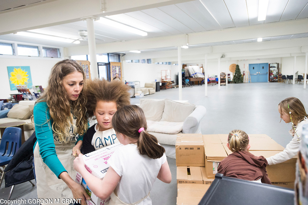 London Rosiere, left, founder of the non-profit group Camp SoulGrow, helps children stock food at the Montauk Food Pantry at St. Therese Church in Montauk, March 14, 2016.