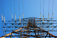 Looking up at an electrical transmission tower.