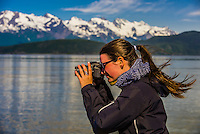 "A tourist aboard the Alaska Fjordlines catamaran ""Fjordland"" snaps a photo while the ship sails down the Lynn Canal, the deepest fjord in North America, between Haines and Juneau, Inside Passage, Southeast Alaska USA."
