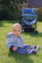 Baby boy sitting on grass in park in front of pushchair,