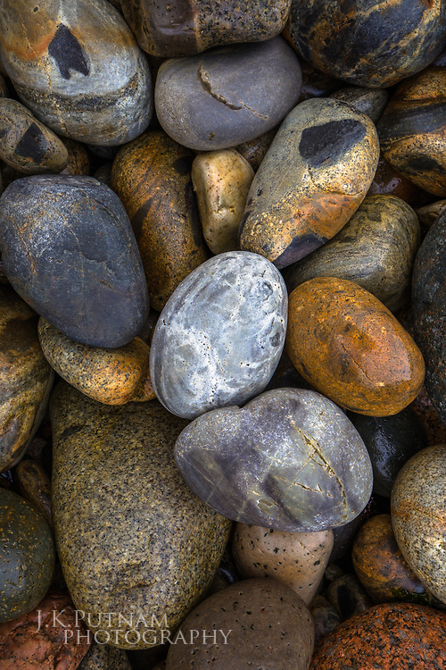 Volcanic and multicolored stones, polished by waves, on a beach in Acadia National Park, Mount Desert Island, Maine.