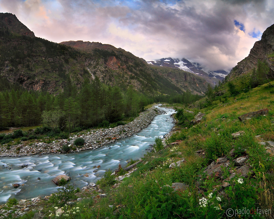 A view at sunset of Valnontey, a small alpine valley in the heart of the Gran Paradiso National Park in Aosta Valley, Italy,  with the glaciers of the Gran Paradiso group in the background