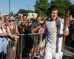 © Licensed to London News Pictures. 23/07/2012. London, UK.  Tim Henman carries the Olympic Torch on day 66 of the Olympic Torch Relay through the London Borough of Wandsworth.  Here he greets fans with the unlit torch, shortly before lighting it and entering Tooting Common where a cauldron will be lit.  Photo credit : Richard Isaac/LNP