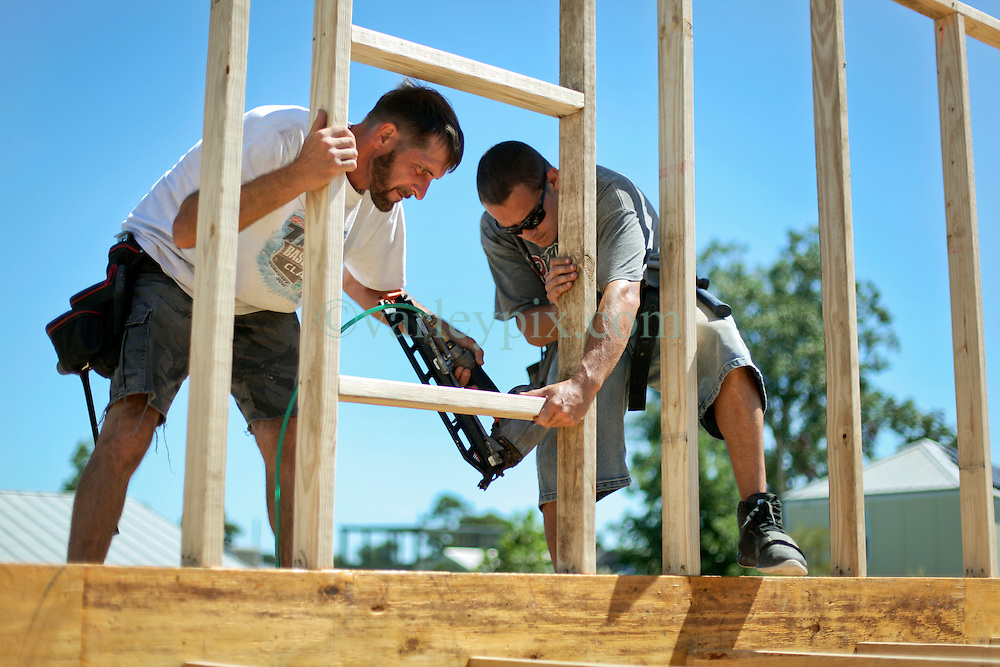 26 August 2015. New Orleans, Louisiana. <br /> Hurricane Katrina revisited. <br /> Rebuilding the Lower 9th Ward. <br /> L/R; Terry Gauxtreaux and Tim Dyar, contractors with Welbilt homes works on a new 'Make it Right' house on Tennessee Street. Eco friendly 'Make it Right' houses inspired by actor Brad Pitt continue to provide hope for the rebirth of the community following the devastation of hurricane Katrina a decade earlier.<br /> Photo credit©; Charlie Varley/varleypix.com.