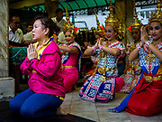 09 NOVEMBER 2017 - BANGKOK, THAILAND: A woman prays while classical dancers she paid for perform at the Erawan Shrine on the 61st anniversary of the shrine's dedication. The Erawan Shrine is one of the most popular shrines in Bangkok. It was dedicated on November 9, 1956, after a series of construction accidents at what was then the Erawan Hotel (since torn down and replaced by the Grand Hyatt Erawan Hotel). The statue in the shrine is Phra Phrom, the Thai representation of the Hindu god of creation Brahma. It is a Hindu shrine popular with Thai and Chinese Buddhists because it is thought that making an offering to the Phra Phrom will bring good fortune.    PHOTO BY JACK KURTZ