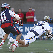 Davey Emala #25 of the Charlotte Hounds is pushed to the ground by Matt Smalley #11 of the Boston Cannons during the game at Harvard Stadium on May 17, 2014 in Boston, Massachuttes. (Photo by Elan Kawesch)