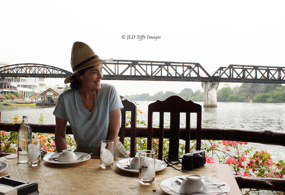 American woman customer at a floating restaurant under the Bridge on the River Kwai at Kanchanaburi,Thailand.