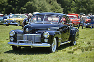 Westbury, New York, USA. June 12, 2016.  Visitor looks at interior of black vintage Cadillac with front chrome grille and bumpers and white wall tires is on display at the Antique and Collectible Auto Show at the 50th Annual Spring Meet at Old Westbury Gardens, in the Gold Coast of Long Island, and sponsored by Greater New York Region, GNYR, Antique Automobile Club of America, AACA. Participating vehicles in the judged show included hundreds of domestic and foreign, antique, classic, collectible, and modern cars.