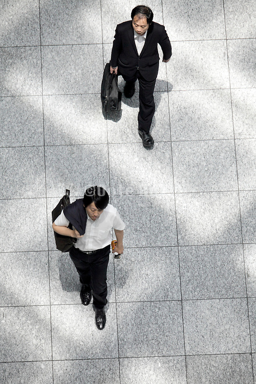 overhead view of business people walking with light from roof pattern on the floor