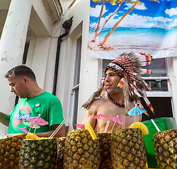 London, August 28 2017. A man in a Native American head dress sells pina coladas on Day Two of the Notting Hill Carnival, Europe's biggest street party held over two days of the August bank holiday weekend, attracting over a million people. © Paul Davey.