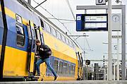 Nederland, Arnhem, 10-12-2015Treinen staan op het centraal station. Reizigers vertrekken of komen aan op het perron. Een man kijkt op zijn telefoon, smartphone, gsm, mobiel, mobieltje terwijl hij de trein instapt.FOTO: FLIP FRANSSEN/ HH