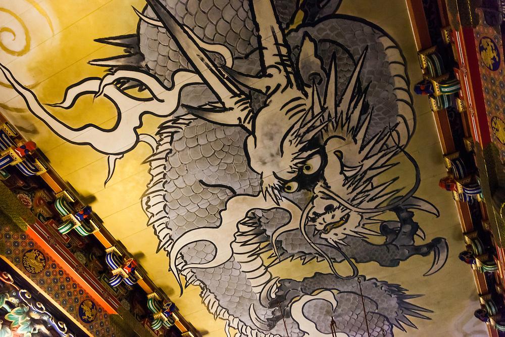 """JAPAN, NIKKO - August 2012 - The Honji-do Temple """"crying dragon"""". This dragon is painted on the ceiling of the temple. It makes a sound like roaring when clappers are struck standing underneath the dragon. Toshogu Shrine is where the famous Shogun of the Edo Period in the 17th century, Tokugawa Ieyasu, was worshiped after his death. It became as luxurious and elaborate as it looks today when the grandson of Ieyasu, the third Shogun Tokugawa Iemitsu, reconstructed it. The engravings on the Yomei-mon Gate are especially overwhelming, provided with every luxury imaginable and redolent in gorgeous colors. site calssified as Japanese Cultural property and world heritage by UNESCO [FR] Le plafond du Honji-do s'orne du """" dragon pleureur """" qui renvoie un écho si l'on frappe des mains au-dessous de lui. Sanctuaire Toshogu - Construit en 1636 à la mémoire de Ieyasu, fondateur du shogunat Tokugawa. Contrairement aux autres sanctuaires shinto, caractérisés par une architecture épurée se fondant dans le paysage environnant, ce sanctuaire est une exubérance de couleurs, d'applications de feuilles d'or et de sculptures en tous genres.Site classé propriete culturelle du Japon et patrimoine mondial de l'UNESCO"""
