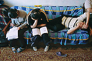 (MODEL RELEASED IMAGE). Khorloo and Batbileg Batsuuri, and their cousin Suvd Erdene do their homework. Ulaanbaatar, Mongolia. Hungry Planet: What the World Eats (p. 229).