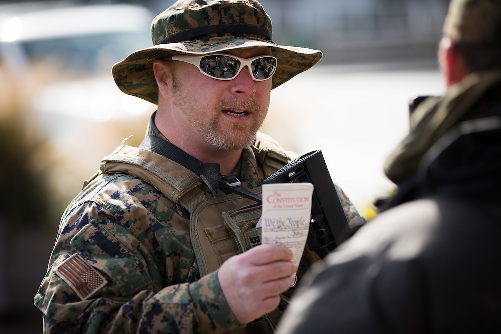 The Georgia Security Force III% militia holds a protest on Marietta Street in downtown Atlanta on Saturday, Feb. 6, 2016. The protest was partly inspired by the death of LaVoy Finicum by federal authorities. Chris Hill, founder of GSF III% and organizer of the protest, talks with passersby. Photo by Kevin D. Liles/kevindliles.com
