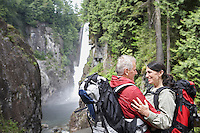 Man and woman embracing carrying backpacks waterfall in background