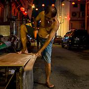 A man sawing a plywood to make a shelf at Jalan Panggong in Kuala Lumpur on November 22, 2017.