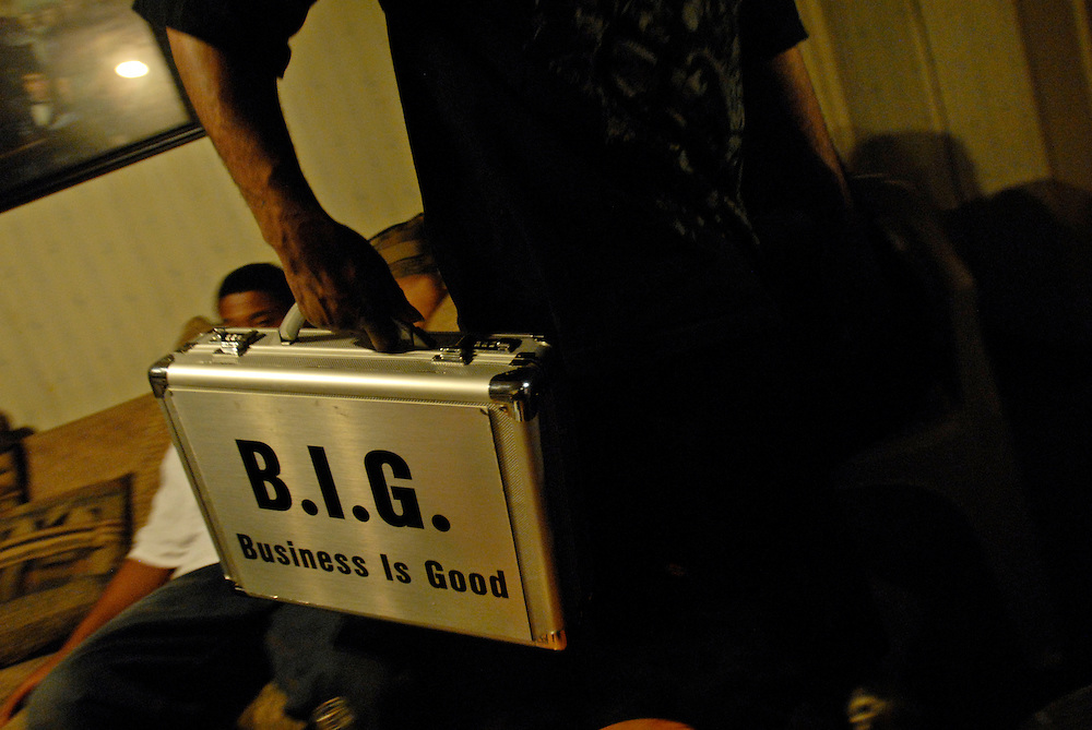 Black, leader of the B-House, removes a suitcase from the room at the B-House during an all night party in Gary, Indiana. Members of the B-House deal in narcotics and prostitution.